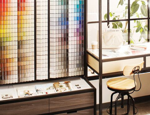 A wall of color chips next to a studio-style desk invites color exploration in a Benjamin Moore store.