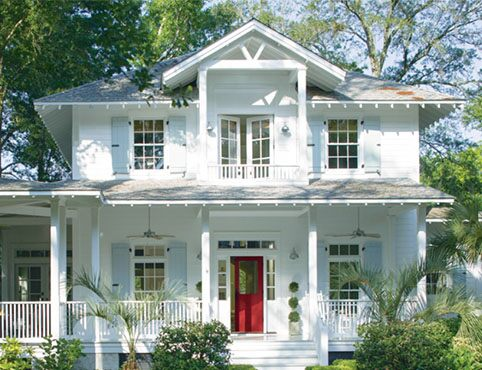 Traditional home with red door and wrap-around porch