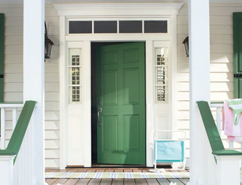 Green front door with matching window shutters