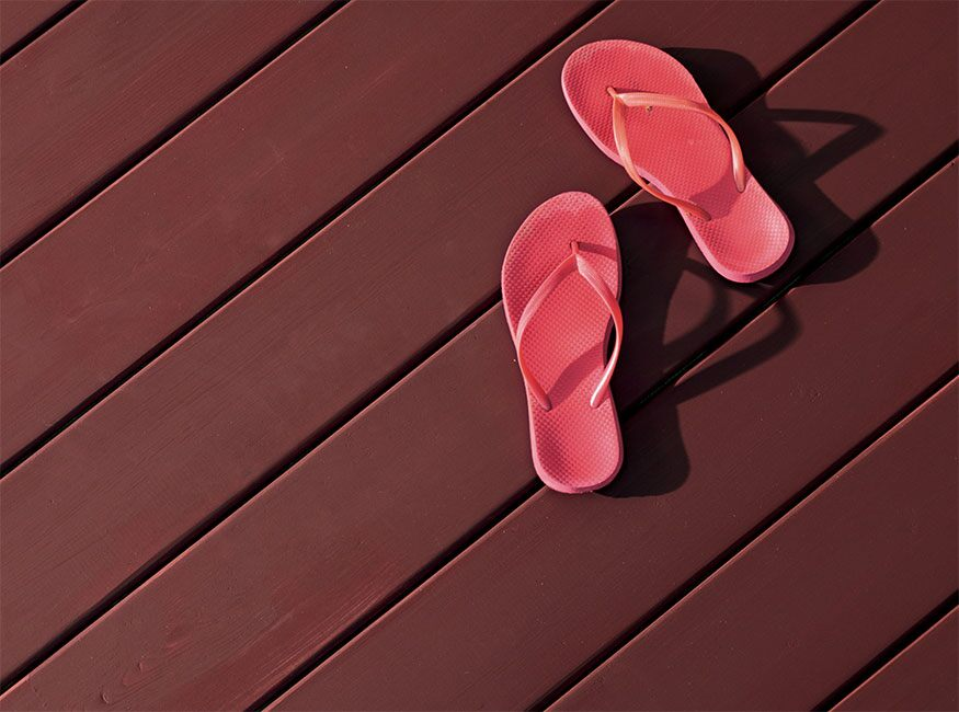 Pink flip flops sit on a cedar deck stained in ARBORCOAT Solid in New Pilgrim Red.