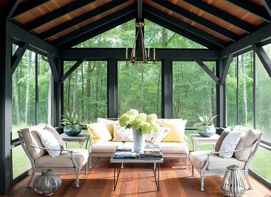 A furniture-filled enclosed porch features a ceiling and floor stained with ARBORCOAT Translucent in Mahogany, while the exposed beams stand out in ARBORCOAT Solid in Black.