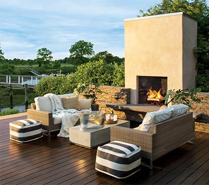 An outdoor deck stained in ARBORCOAT Semi Solid in Cordovan Brown features cushion-covered couches, a bucket of cold drinks and a fireplace.