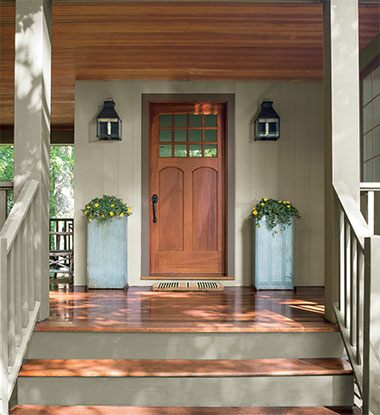 An exterior porch with pillars of yellow flowers features siding and railings stained in ARBORCOAT Solid in Sea Gull Gray, a door and porch floor stained with ARBORCOAT Translucent Cedar, and a ceiling stained in ARBORCOAT Translucent Teak.