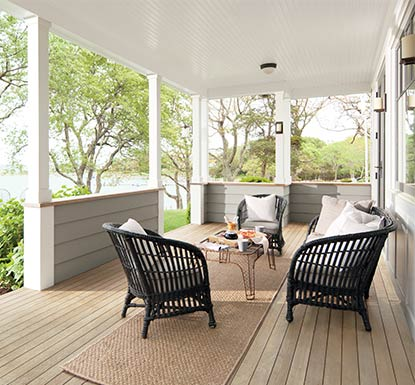 A backyard porch overlooking a lake with a boat features a deck and railings stained in ARBORCOAT Translucent in Silver Gray.