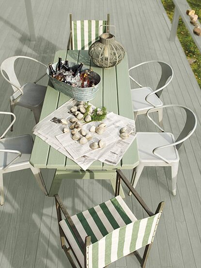 A light grey deck and mossy green wood table welcomes guests with a tub of icy beers and freshly caught clams.