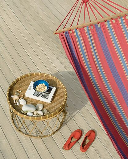 A  striped hammock, wicker table and a pair of espadrilles sets a beachy vibe against a neutral deck.