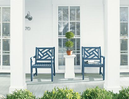Two deep blue arbor chairs provide a sophisticated pop of color against a white deck.