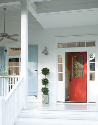 Red front door, white porch, and light blue shutters