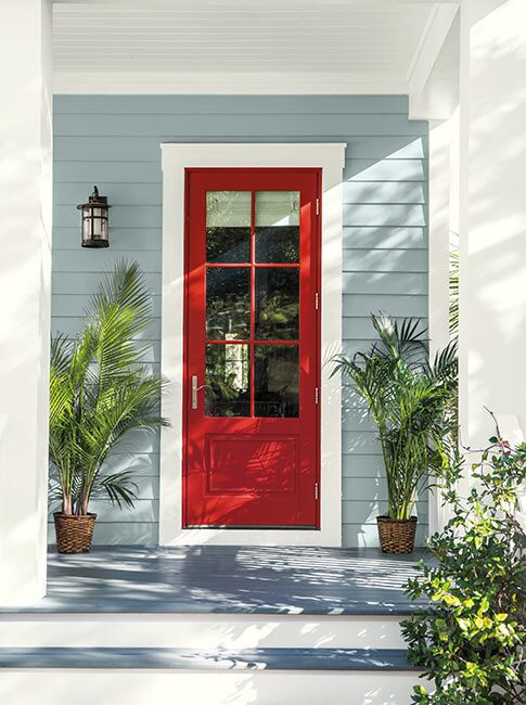 A welcoming front entrance with a red-painted door and potted plants