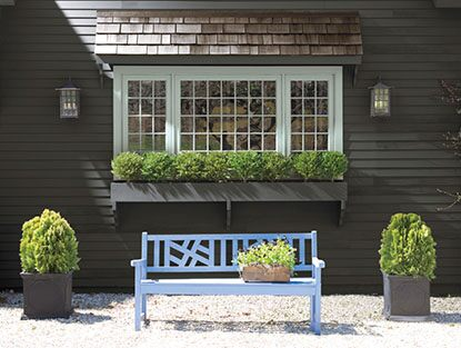 Blue bench outside home with plants in windowsill