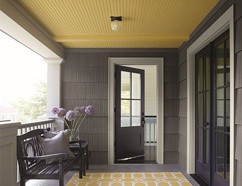 A covered porch area with a yellow ceiling painted in Marblehead Gold 2120-30