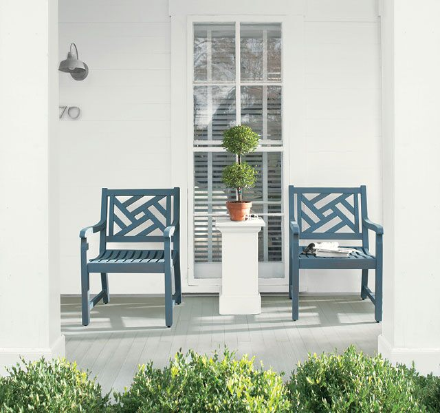 White front porch with blue chairs all stained in ARBORCOAT ® Exterior Stain, Solid with porch floor in Cliffside Gray HC-180, Chair in Hamilton Blue and Siding in White.