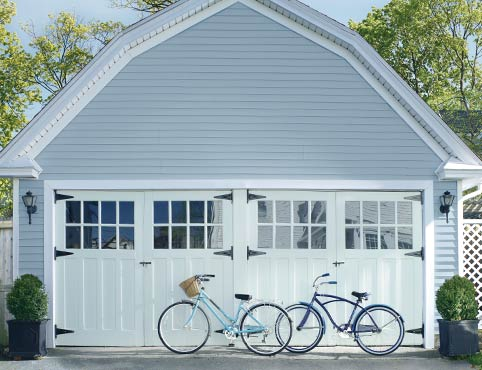 A barn-style vinyl-sided garage features large white doors.