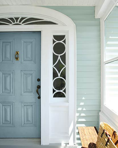 Gray vinyl siding frames a front door in a deeper gray from an enclosed front entryway.