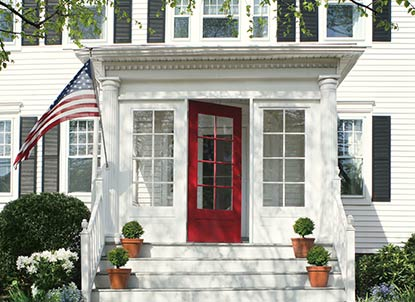 A white vinyl-sided home with a red window-paned front door and enclosed front portico welcomes guests.