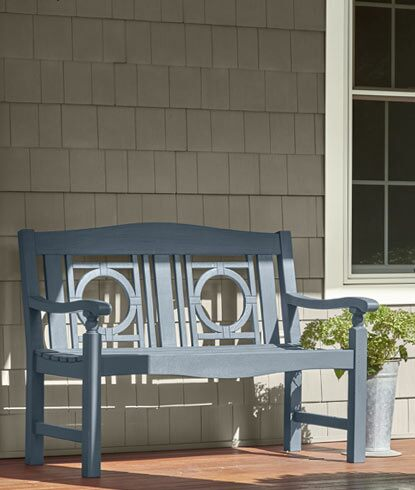 Vinyl siding home exterior with white-painted trim and a blue-gray bench