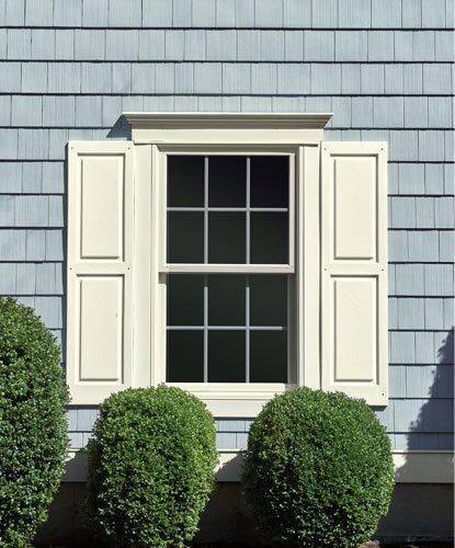 A home's vinyl siding is painted in blue-gray with white-painted trim