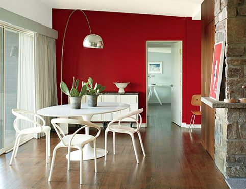 A contemporary dining room with a red accent wall in Caliente AF-290.