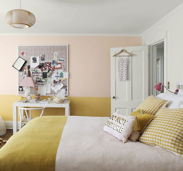 Teen girl bedroom with accent wall painted in light pink and yellow.