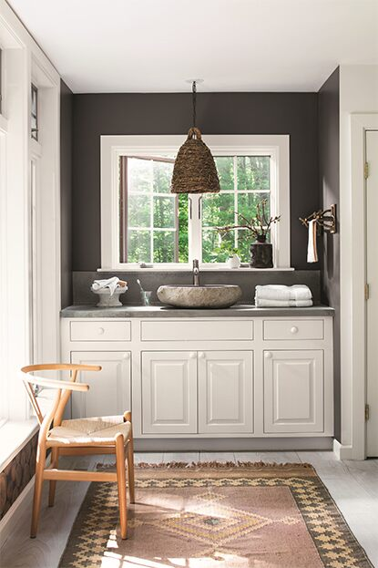 Black bathroom walls with white vanity and moroccan rug.