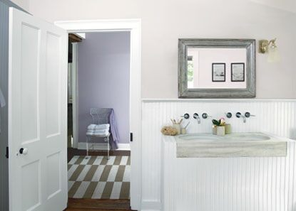 Calm, cozy bathroom with farm sink vanity and purple wall
