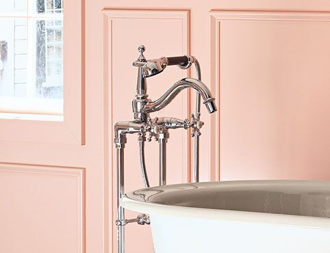 Chic pink bathroom with clawfoot tub and French décor and Kohler finishes