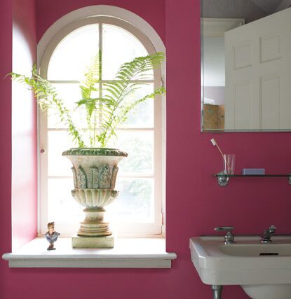 A bold pink painted bathroom with a potted plant and arched window.