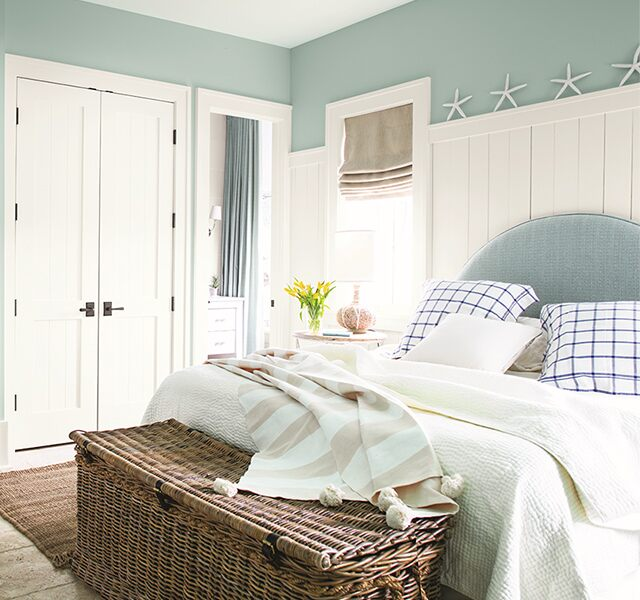 Light blue bedroom walls with white built in desk, a large bed with light and dark blue pillows and comforter.