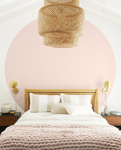 Light bedroom with white walls and a large light pink circle behind white bed with pink throw blanket and a basket chandelier.