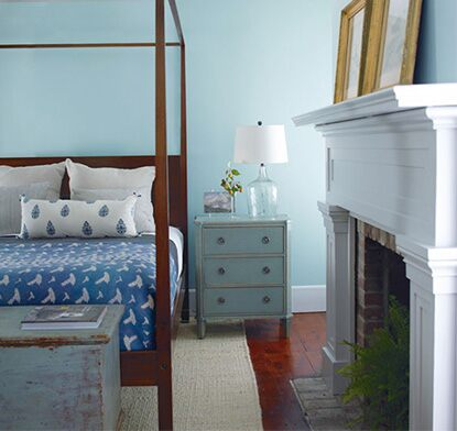 Blue bedroom with colonial style furnishings and fireplace with brick and crown molding
