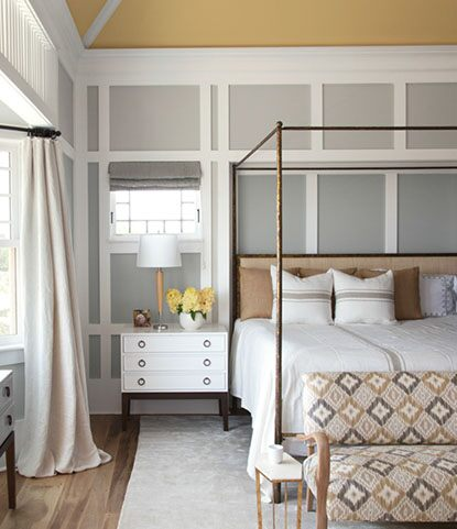 Cozy bedroom with bay windows and paneled walls