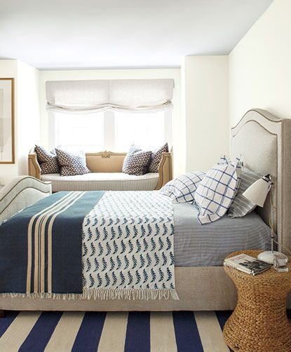 Bedroom with nautical-inspired blue striped rug and walls painted in Icicle OC-60.