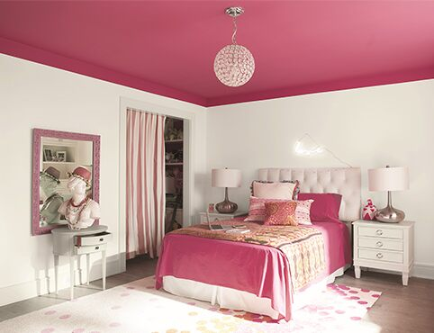 White bedroom walls with a bright pink ceiling and matching pink bedding with two side tables and lamps.