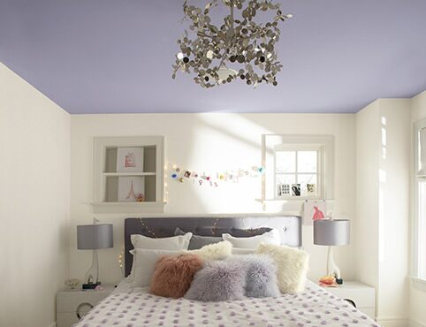 An airy teen bedroom with ceiling in light purple paint color.