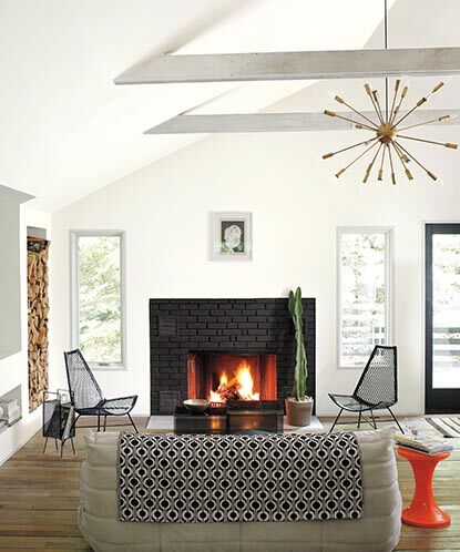 A modern white living room with black brick fireplace and hardwood floors.