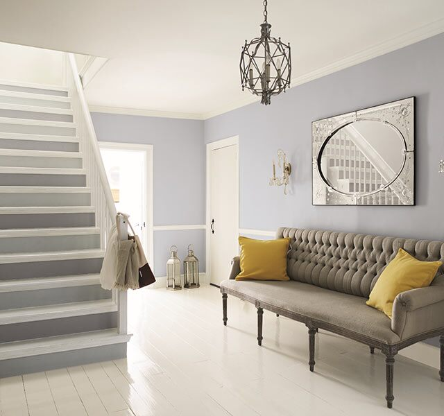 Light blue-gray and white entryway with classic furniture accents.