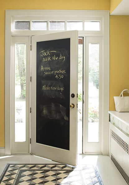 A chalkboard door in a yellow entryway provides a way for families to leave notes for one another.