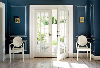 A royal blue chalkboard adds depth to a living room with French doors.