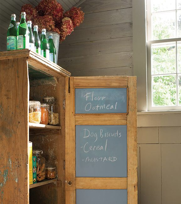 A shopping list adorns the chalkboard door of a rustic-looking pantry.