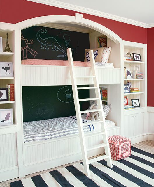 A bedroom features built-in bunk beds with a chalkboard wall, bookcases and striped rug.