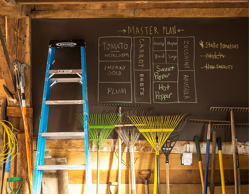 A family uses an in-shed chalkboard to track their garden's process.