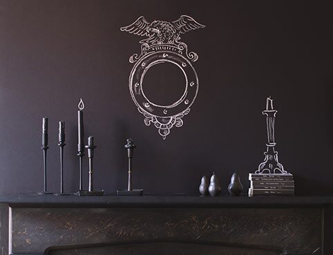 Chalkboard paint lends an artistic flare to the space above a gothic mantel.