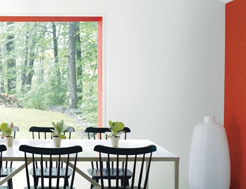 White dining room with orange accent wall and black dining chairs.