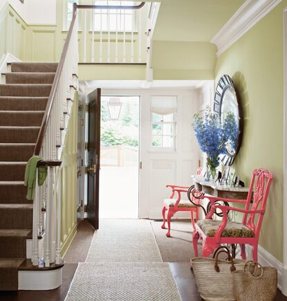 A front door opens into a pale green entryway featuring a console table and two colorful side chairs.