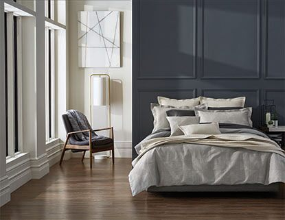 A bold accent wall complements a navy and gray bedding set