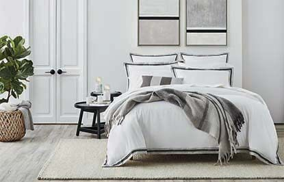 A white bedroom with gray-accented bedding