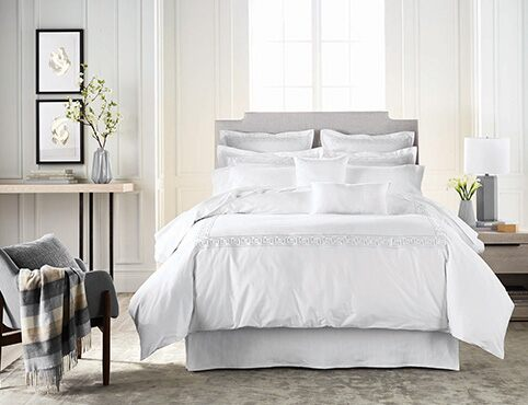 The palest gray walls flatter a bedroom with fluffy white bedding.