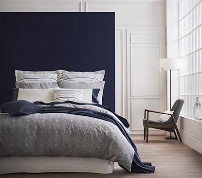 A serene bedroom features Benjamin Moore paint and Gluckstein Home bedding.