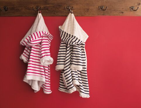 Red wall with a wooden plank coat rack, two striped children's robes, one in pink and one in black.