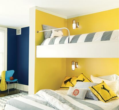 A yellow-painted kid's bedroom with gray and white bunk beds.